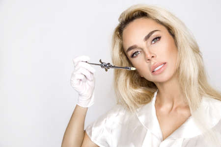 Aesthetic medicine. Beautiful woman face gets a beauty injection. Lifting and removal of facial wrinkles. Face contouring. Perfect face model on white background.