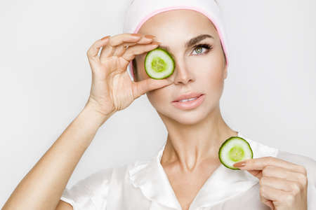 Beautiful blonde woman with moisturized face mask. Beauty spa. Skincare concept. Woman with facial mask. Imagens