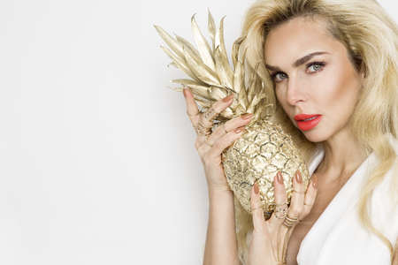 Happy elegant young woman holding a gold pineapple on a white background. Spring summer fashion female model. Summertime.