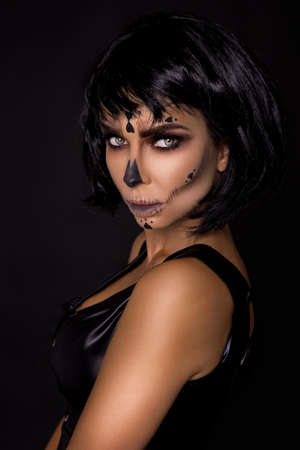 Portrait brunette woman in Halloween makeup on a black background in the studio. Makeup as skeleton, monster and witch. Halloween makeup. Reklamní fotografie