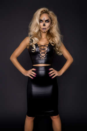 Sexy blonde woman in Halloween makeup and latex costume on a black background in the studio. Halloween makeup and costume. Sexy witch. Reklamní fotografie