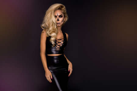 Sexy blonde woman in Halloween makeup and latex costume on a black background in the studio. Halloween makeup and costume. Sexy witch.