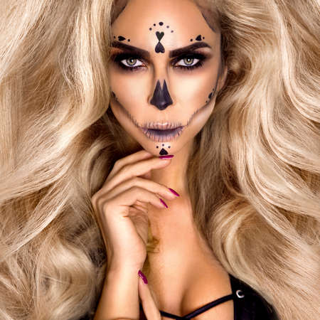 Halloween Sexy Witch portrait. Beautiful young woman in witches makeup with long curly blonde hair. Halloween makeup, visage. Wide Halloween party art design - Image Reklamní fotografie
