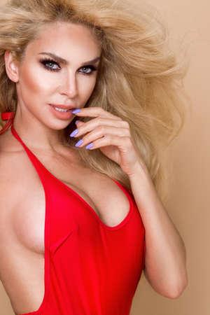 Sexy busty blonde lifeguard woman with red bikini is holding lifeguard float on beige, pastel background and sensually posing. Bikini hot model. Sexy lifeguard. Bikini fashion.