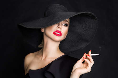 Sexy woman in elegant hat and with red lips blowing smoke, isolated on black. Femme fatale. Elegant lady with cigarette. Archivio Fotografico