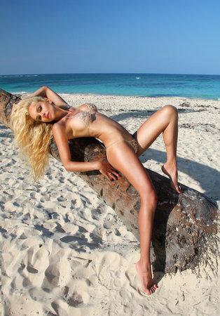 Sexy model in elegant bikini on the sun-tanned slim and shapely body is posing on the Caribbean beach. Hot body woman in bikini in Dominican Republic. Bikini model - concept.