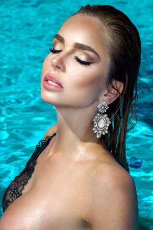 Elegant woman in the elegant bikini on the sun-tanned slim and shapely body is posing in the swimming pool in Caribbean luxury resort. Bikini fashion. Elegance. Summertime.