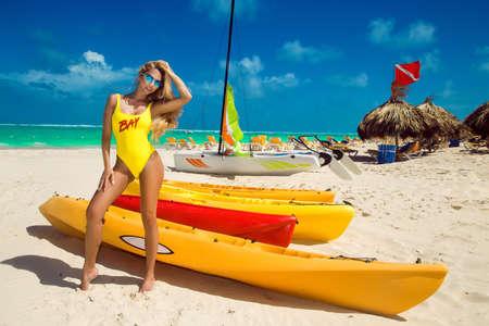 Beautiful blonde model girl in bikini at the seaside of the Caribbean beach. Luxury travel, summer vacation, fashion style and water sports. Sexy lifeguard girl. Bikini fashion. Baywatch.