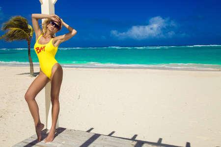 Beautiful blonde model girl in bikini at the seaside of the Caribbean beach. Luxury travel, summer vacation, fashion style. Sexy lifeguard girl with lifeguard float. Bikini fashion. Baywatch.