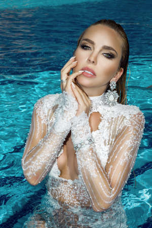 Summer fashion. Elegant woman in white lace dress on the sun-tanned slim and shapely body is posing in the swimming pool. Beauty face model with perfect makeup. Luxury and elegant woman.