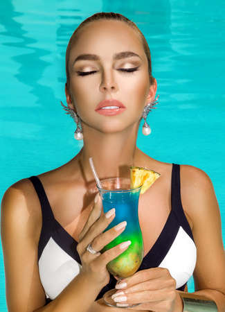 Beautiful young woman with perfect skin and trendy nails is posing in pool with colorful drink. Portrait of beauty model with summer makeup and elegant manicure. Spa, skincare and wellness. Foto de archivo