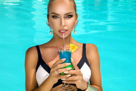 Beautiful young woman with perfect skin and trendy nails is posing in pool with colorful drink. Portrait of beauty model with summer makeup and elegant manicure. Spa, skincare and wellness.