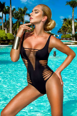 Elegant woman in the black elegant bikini on the sun-tanned slim and shapely body is posing in the swimming pool - Image. Luxury Caribbean resort. Travel. Beachwear fashion. Archivio Fotografico