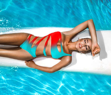 Elegant woman in the colorful bikini on the sun-tanned slim and shapely body is posing near the swimming pool - Image Imagens