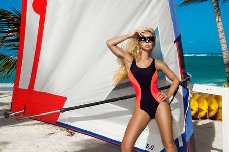 Beautiful girl, surfer in a bikini on a Caribbean beach. Caribbean beach, sand and palm trees. Sport and recreation. Swimsuit fashion. Swimwear. Foto de archivo