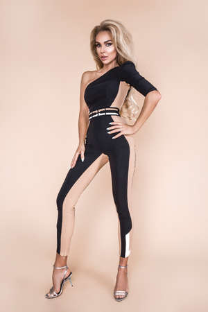 High fashion model in studio. Beautiful lady in elegant jumpsuit and high helles shoes. Spring fashion style. Elegant model posing in fashionable outfit - Image