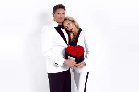 Happy beautiful couple posing on white background and holding flower box with red heart. Valentine's day, wedding - Image