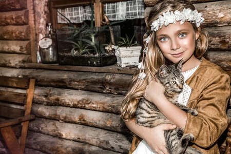 Portrait of a small cute child with tenderness and love a cat and smiles with happiness. Little girl relaxing on park with her kitten. Child in white communion dress is kissing a cat. Spring fashion