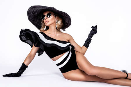 Bikini fashion. Elegant tanned woman in a black and white bikini and in big hat isolated on white background in studio. Swimsuit fashion. Elegance. Summer fashion. Hat woman.