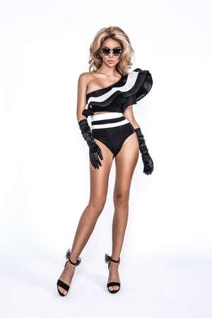 Bikini fashion. Elegant tanned woman in a black and white bikini and sunglasses isolated on white background in studio. Swimsuit fashion. Elegance. Summer fashion. Stockfoto
