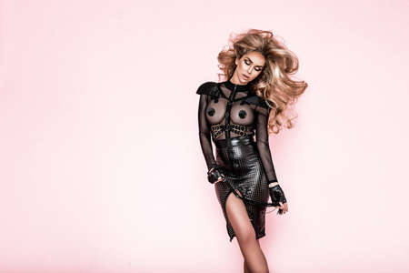 Lingerie fashion. Beautiful sexy blonde woman in latex lingerie on a pink background in studio. Hot lingerie model.
