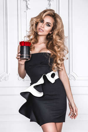 Beautiful woman in elegant black and white dress and perfect hairstyle is holding flower box with red roses on white background. Woman with gift. Glamor fashion model. Standard-Bild