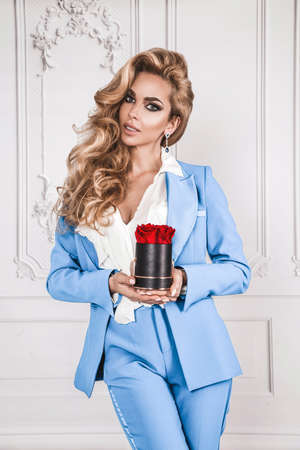 Beautiful woman in elegant suit and perfect hairstyle is holding flower box with red roses on white background. Woman with gift. Glamor fashion model.