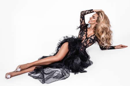 Elegant fashion. Stunning blonde woman in elegant long black dress and perfect hairstyle on white background. Luxury evening fashion. Glamor fashion model. Elegance.