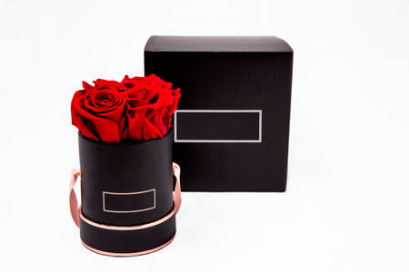 Elegant black Flower box with red roses. Beautiful red flowers in black box. Glamor vogue flower box Isolated on white background. Fashion flowers. Christmas and birthday Gift. Standard-Bild