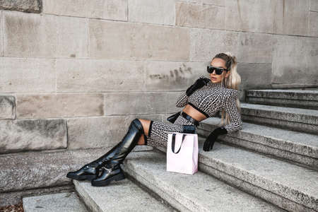 High fashion. Sexy woman in elegant outfit and fashionable boots is posing in the city. Fashion model in stylish outfit. Elegance. Autumn, winter fashion. Standard-Bild
