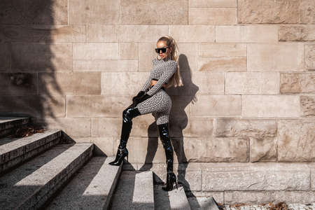 High fashion model. Sexy woman in elegant outfit and fashionable boots is posing outdoor. Fashion model in stylish outfit. Elegance. Spring, summer fashion.