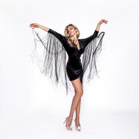 Elegant fashion. Stunning blonde woman in elegant designer dress with fringes isolated on white background. Luxury evening fashion. Glamour fashion model. Elegance.