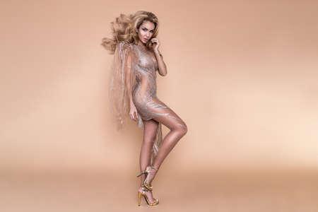 Elegant fashion. Stunning blonde woman in elegant designer jumpsuit and perfect hairstyle on beige background. Luxury evening fashion. Glamour fashion model. Elegance. Standard-Bild