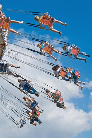 kids on swinging carousel at high blue sky photo