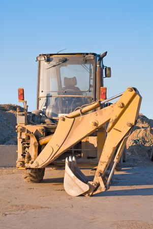 compact track loader: Resting compact excavator with piled backhoe Stock Photo