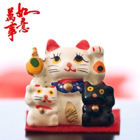 Japanese Maneki-nekos (Lucky cat) on abstract background with New Year wishes photo