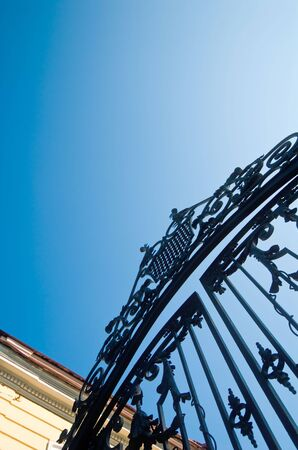 Wrought iron gate in classic style over clear sky photo