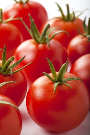 pomidory: Zbliżenie czerwonych małych pomidorów izolowanych na białym tle.