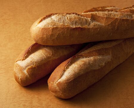 french bread: The whole bread on a brown background.