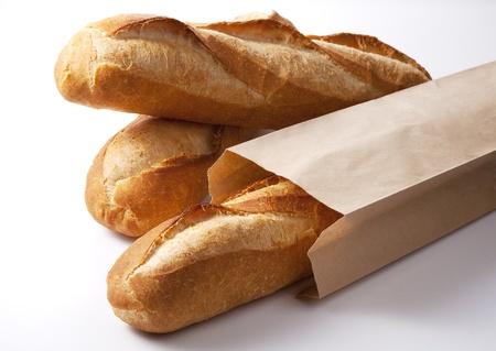 白で隔離される紙袋でフランスのバゲットのクローズ アップ。 写真素材