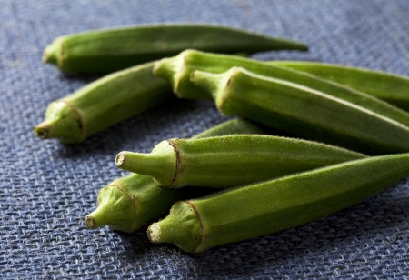 Lady fingers (Okras - Gumbos) on blue cloth photo