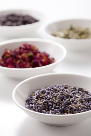 Assortment of dry medicinal herbs in bowls photo