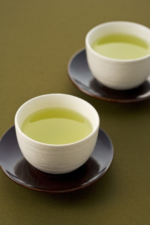 Green tea in a white cup on a dark background photo