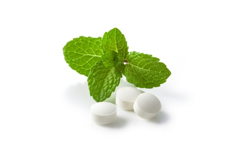 peppermint: Fresh green mint and white pills isolated on white