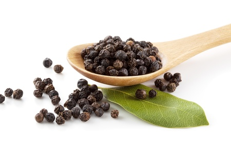 Black pepper in wooden spoon with laurel