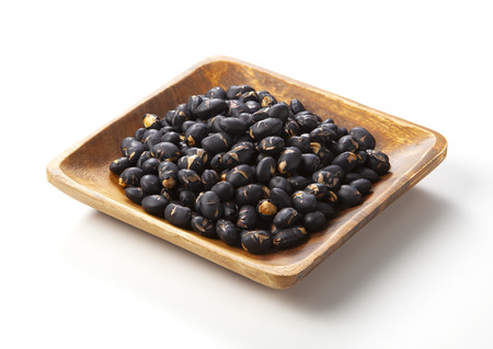 black beans in dark wooden bowl isolated on white.