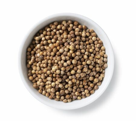 Coriander seeds in a plate placed on a white background Imagens