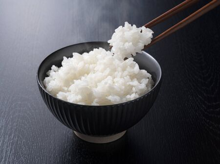 scooping rice with chopsticks on the black background Foto de archivo