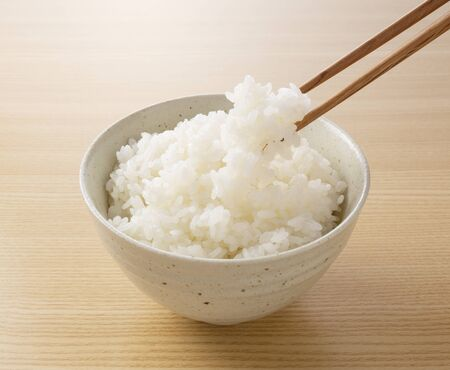 A close-up shot of him scooping rice with chopsticks against a wooden background Stock Photo