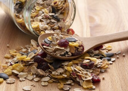 Close-up shot of a wooden spoon with granola and container placed against a wooden background